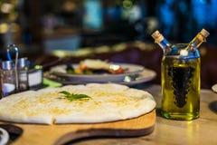 Свеже испеченная пицца focaccia с сыр пармесаном на деревянной стойке на деревянном столе Стоковые Фото