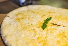 Свеже испеченная пицца focaccia с сыр пармесаном на деревянной стойке на деревянном столе с бутылкой оливкового масла Стоковые Фотографии RF