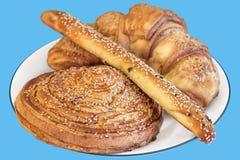 Свеже испеченное печенье слойки круассана взбрызнутое при семена сезама изолированные на голубой предпосылке Стоковые Фото