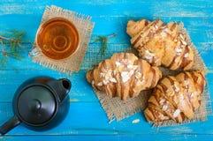 Свеже испеченные круассаны с хлопьями миндалины, баком чая и чашкой чаю Стоковые Фотографии RF