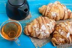 Свеже испеченные круассаны с хлопьями миндалины, баком чая и чашкой чаю на голубой деревянной предпосылке Стоковое Изображение