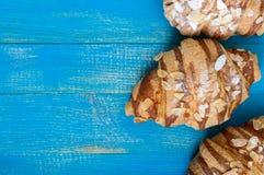 Свеже испеченные круассаны с хлопьями миндалины, на голубой деревянной предпосылке Стоковое Изображение RF