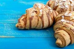 Свеже испеченные круассаны с хлопьями миндалины, на голубой деревянной предпосылке Стоковое Фото