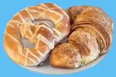 Свеже испеченный крен и крендель улитки печенья слойки круассана сезама, который служат на белой плите изолированной на голубой п Стоковое Фото
