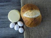 Свеже испеченный хлеб с яичками и сыр пармесаном затем на сыре Nigella, яичка и чеддера на деревянном поле Стоковые Фотографии RF