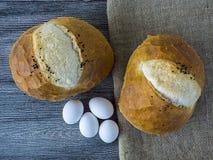 Свеже испеченный хлеб с яичками и сыр пармесаном затем на сыре Nigella, яичка и чеддера на деревянном поле Стоковые Фото
