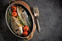 2 свеже испеченных рыбы dorado с тимианом, томатами вишни, красным луком и лимоном в медной сковороде Стоковые Фото