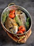 2 свеже испеченных рыбы dorado с тимианом, томатами вишни, красным луком и лимоном в медной сковороде Стоковое Изображение RF