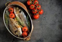 2 свеже испеченных рыбы dorado с тимианом, томатами вишни, красным луком и лимоном в медной сковороде Стоковое фото RF
