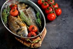 2 свеже испеченных рыбы dorado с тимианом, томатами вишни, красным луком и лимоном в медной сковороде Стоковое Фото