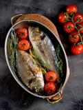 2 свеже испеченных рыбы dorado с тимианом, томатами вишни, красным луком и лимоном в медной сковороде Стоковые Изображения