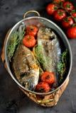 2 свеже испеченных рыбы dorado с тимианом, томатами вишни, красным луком и лимоном в медной сковороде Стоковые Изображения RF