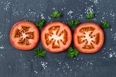 Свеже отрезанный томат на черной предпосылке камня шифера Стоковое Фото
