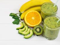 Свеже подготовленный smoothie авокадоа, банана, петрушки, лимона, апельсина и кивиа на белом деревянном столе Еда вегетарианца ди Стоковое Фото