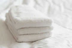 Свеже помытые белые полотенца руки штабелированные на белой кровати Стоковые Изображения RF