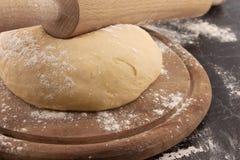 Свеже подготовленные тесто и вращающая ось на деревянной доске Стоковые Изображения