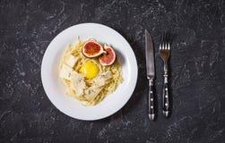 Свеже сваренные макаронные изделия с смоквами, яичный желток, сыр над деревенской каменной доской Взгляд сверху стоковые изображения rf