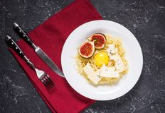 Свеже сваренные макаронные изделия с смоквами, яичный желток, сыр украшенный с салфеткой над деревенской каменной доской Взгляд с стоковая фотография rf