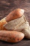 Свеже сжатые органические сладкие картофели в сумке мешковины на деревянном столе Стоковое фото RF