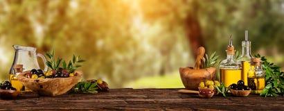 Свеже сжатые ягоды оливок в деревянных шарах и отжатом масле i Стоковые Изображения