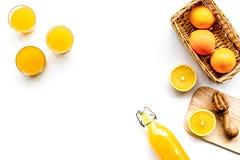 свеже сжатый помеец сока Juicer и куски апельсинов на белом copyspace взгляд сверху предпосылки Стоковое фото RF