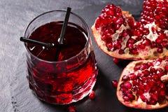 Свеже сжиманный сок гранатового дерева с соломами на серой предпосылке Плодоовощ зрелых, сочных, органических и преимущества вени Стоковые Изображения
