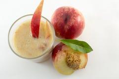 Свеже сжиманный сок персика и свежие персики на белизне Стоковое Изображение