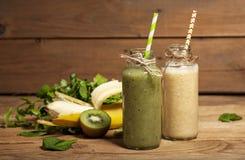 Свеже смешанные smoothies зеленого цвета и банана в стеклянных бутылках с соломами стоковые изображения rf