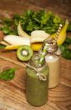 Свеже смешанные smoothies зеленого цвета и банана в стеклянных бутылках с соломами стоковая фотография rf