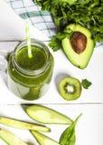 Свеже смешанный зеленый smoothie в стекле с соломой деревянное предпосылки белое Стоковая Фотография RF