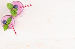 Свеже смешанный фиолетовый smoothie плодоовощ голубики в стекле раздражает с соломой, листьями мяты, взгляд сверху Стоковая Фотография