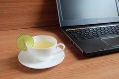 Свеже сок лайма в белой чашке, и компьтер-книжке Стоковые Фотографии RF