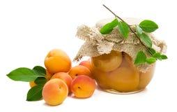 Свежие абрикосы с зелеными листьями, вареньем в стеклянном опарнике стоковое фото