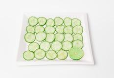 свежие аппетитные отрезанные зеленые огурцы с известкой соединяют в керамической плите Стоковые Фотографии RF