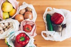 Свежие бакалеи в многоразовых сумках eco и овощи в пластиковой сумке полиэтилена на деревянном столе Пластмасса пользы запрета од стоковая фотография