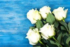 Свежие белые розы на голубой деревянной предпосылке Стоковые Изображения RF