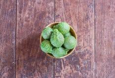 Свежие бергамот и кусок бергамота в деревянном шаре Стоковая Фотография