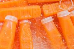 Свежие бутылки апельсинового сока на льде Стоковые Изображения