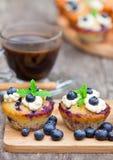 Свежие булочки с голубикой и чашкой кофе на деревянном backgro Стоковые Изображения RF