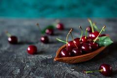 Свежие вишни в деревянной чашке на темной предпосылке Стоковые Изображения