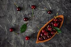 Свежие вишни в деревянной чашке на темной предпосылке Стоковое Изображение