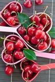 Свежие вишни в измеряя чашках Стоковое Изображение