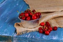 Свежие вишни в старой кружке металла Свежая кружка металла вишен на старом деревянном столе Стоковое Изображение
