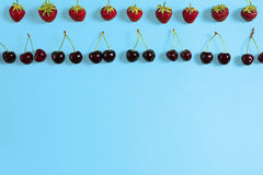 Свежие вишни и клубники на голубой предпосылке, взгляд сверху Стоковое Фото