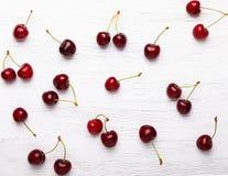 Свежие вишни на белой деревянной предпосылке Стоковое Изображение
