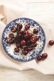 Свежие вишни на блюде на таблице Стоковая Фотография