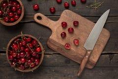 Свежие вишни на деревянной доске с ножом на деревянном столе Стоковая Фотография RF