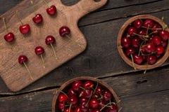 Свежие вишни на деревянной доске с предпосылкой деревянной доски на деревянном столе Стоковое фото RF