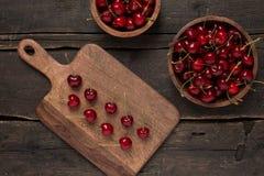Свежие вишни на деревянной доске с предпосылкой деревянной доски на деревянном столе Стоковые Фото
