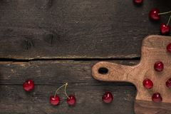 Свежие вишни на деревянной доске с пустым космосом на деревянном столе Стоковые Фотографии RF